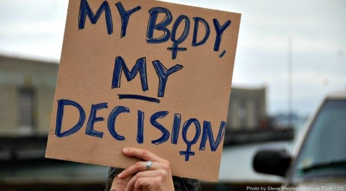 "Hand holding sign that says ""My body my decision"""