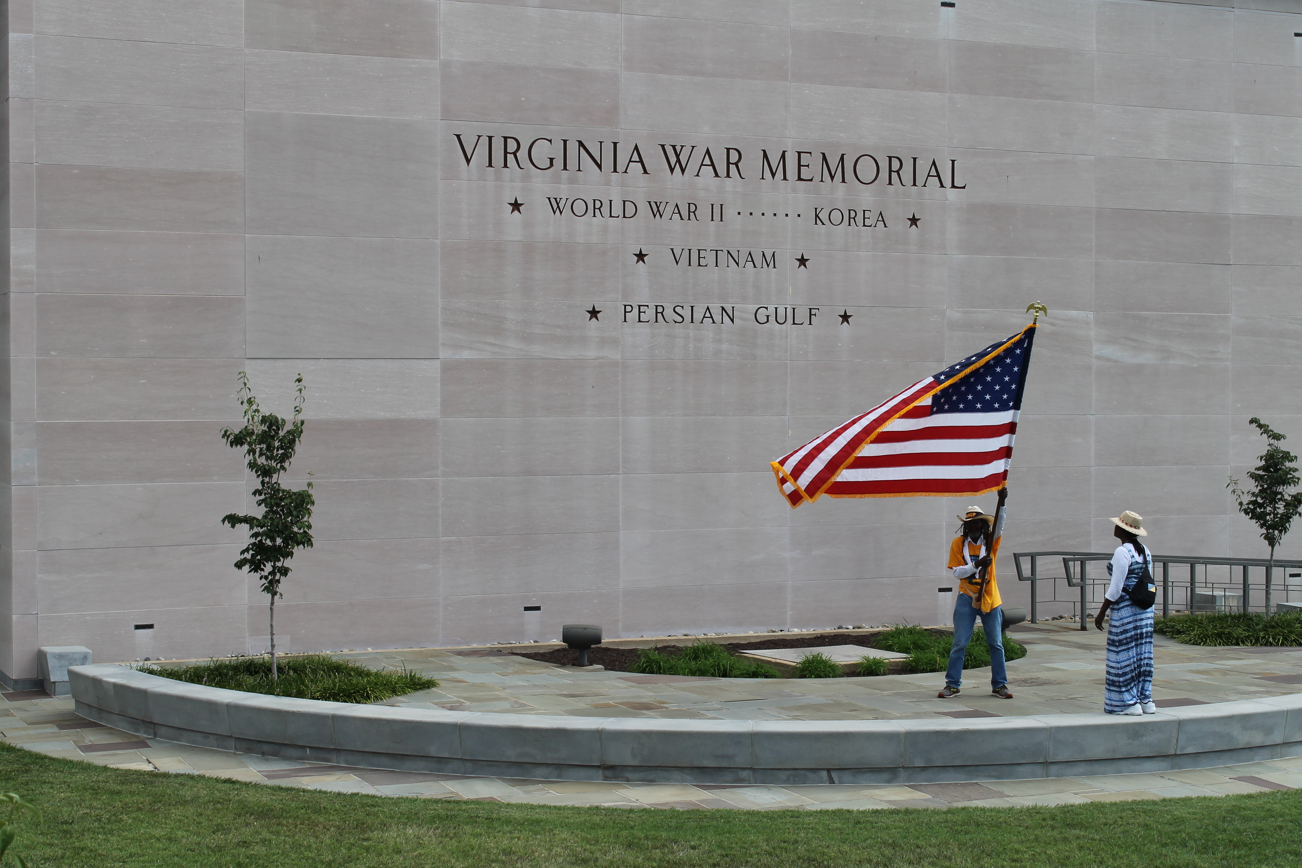 Middle Passage waving American flag in front of the Virginia war memorial