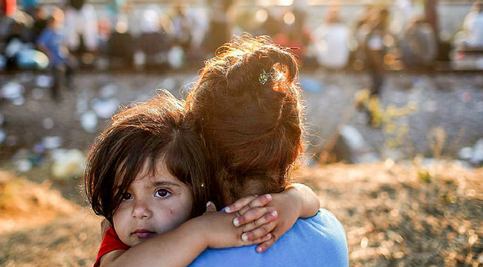 refugee child held by adult