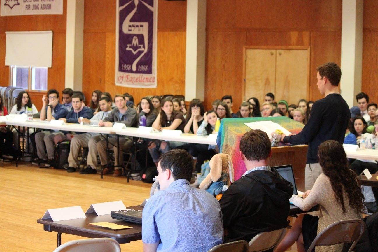 Sam Ressin presenting at NFTY MAR asefah, teens looking on