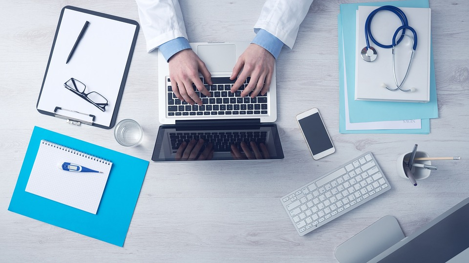 doctor at desk typing on computer