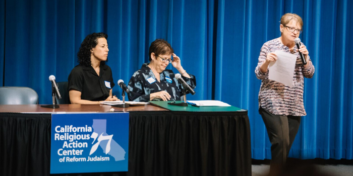 two women sitting behind a desk and one woman speaking with a microphone