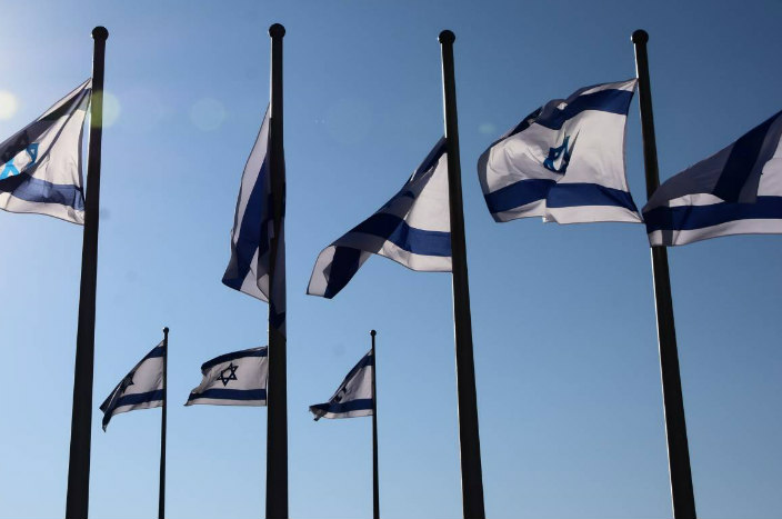 A few Israeli flags on flagpoles against a blue sky background