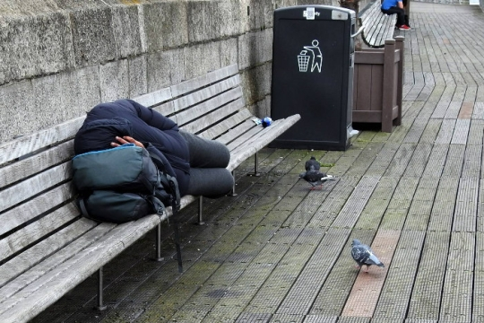 Homeless individual sleeping on a bench outdoors